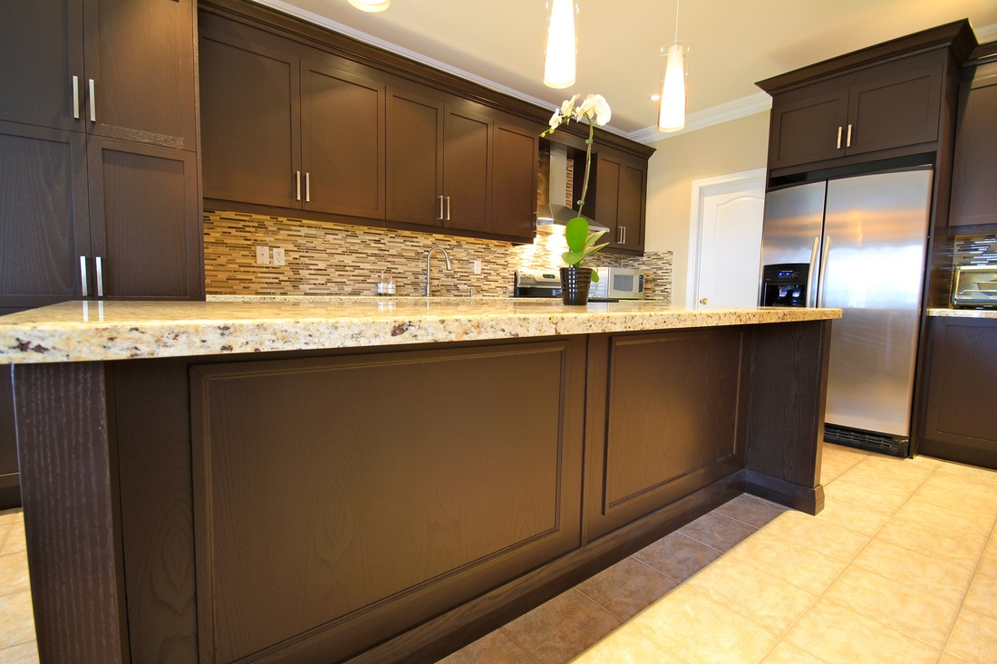 A spacious kitchen with dark colored cabinets